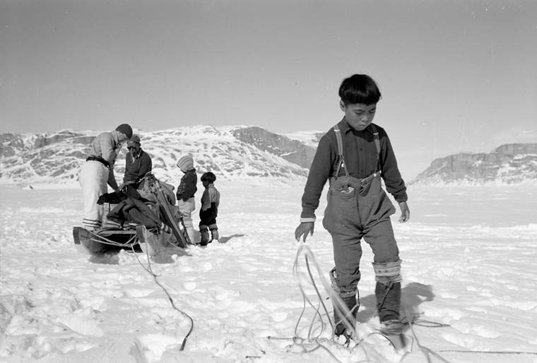 An Inuit boy preparing to set up camp in White Bay, Eclipse Sound, North West Territories, with the mountains of Baffin Island in the background. 1952. © Library and Archives Canada.