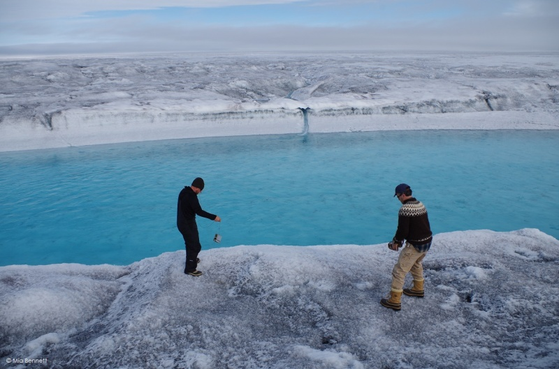Throwing a level logger to measure temperature and pressure into a supraglacial river, Greenland. August 2014.