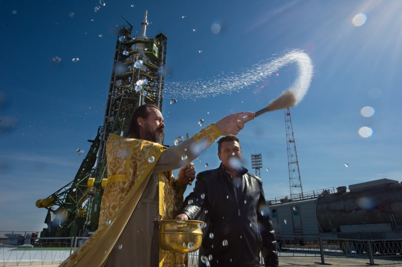 A Russian Orthodox priest blesses the media at the Baikonur Cosmodrome launch pad in Kazakhstan in September 2014, a few days before launch. Will this priest bless the soldiers on Kotelny Island soon, too? Photo: NASA