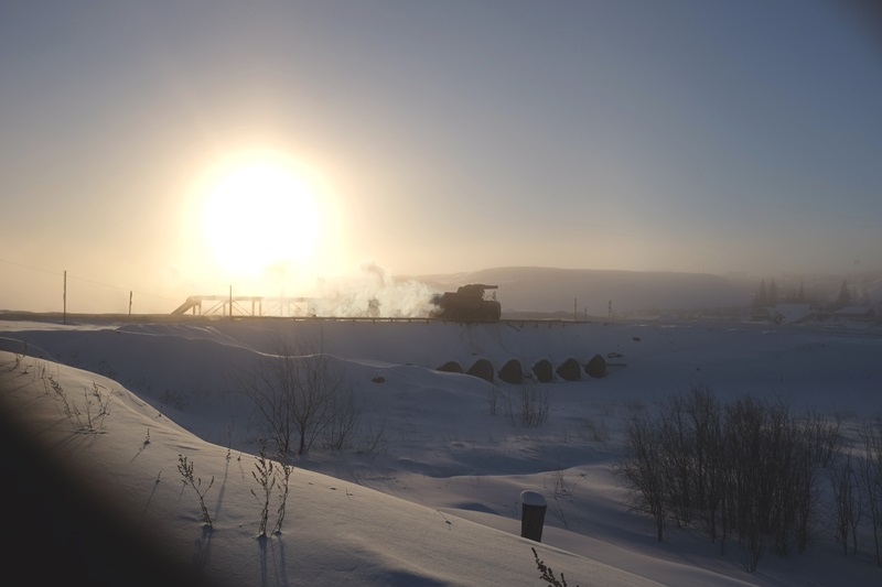 A truck in Mirny, Sakha Republic (Yakutia), Siberia leaving the nearby open-pit diamond mine at sunrise.