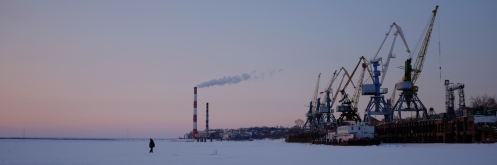 A man looks at the port on the frozen Amur River in Khabarovsk, Russia.